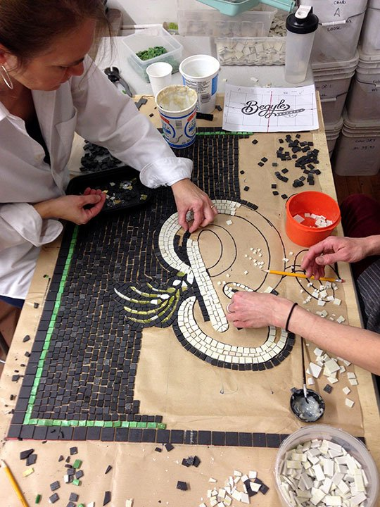 Two women working on begyles mosaic