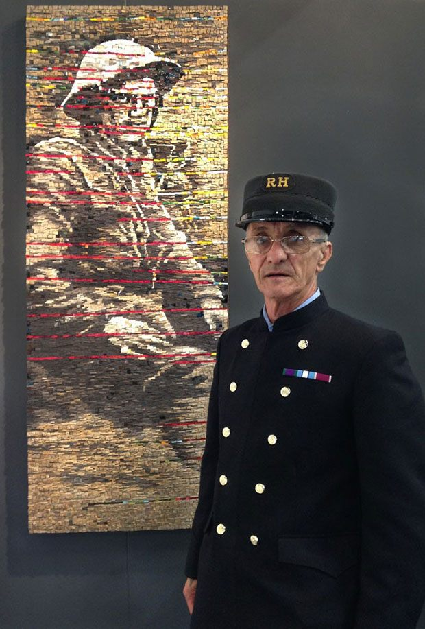 Old soldier standing next to mosaic