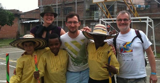 Gary posing for photo with two adults and several columbian children